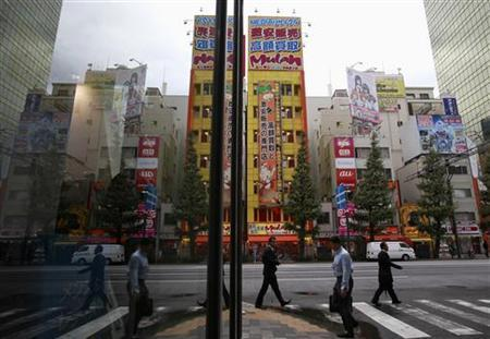 People are reflected on a window as they walk through Tokyo's Akihabara district in Tokyo October 23, 2012. REUTERS/Yuriko Nakao/Files
