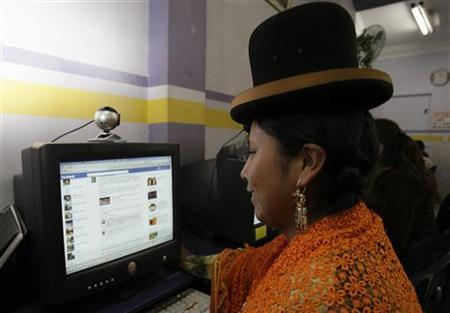 A cholita (Andean woman) looks at her facebook page at a public internet shop in La Paz February 14, 2012. REUTERS/David Mercado/Files