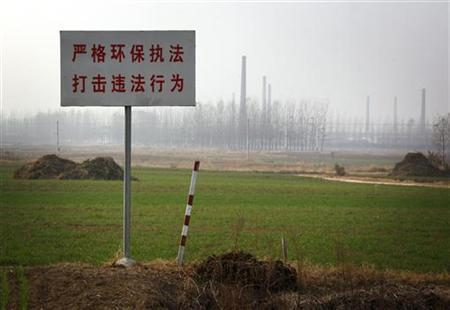 Chimneys from the huge state-owned lead smelter are visible behind a sign that reads, ''Strict environmental protection law enforcement, crack down on illegal behaviors'' in the town of Tianying, Anhui Province, November 19, 2012. REUTERS/David Gray/Files