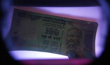 A man uses an electronic machine to check a rupee note at a money exchange shop in Siliguri May 18, 2009. REUTERS/Rupak De Chowdhuri/Files