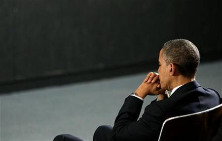 U.S. President Barack Obama prays during a vigil held at Newtown High School for families of victims of the Sandy Hook Elementary School shooting in Newtown, Connecticut December 16, 2012. Obama is visiting Newtown High School to meet with the families of the victims and to thank first responders to the school shooting here that was one of the deadliest such incidents in the nation's history. REUTERS/Kevin Lamarque (UNITED STATES - Tags: POLITICS CRIME LAW EDUCATION)