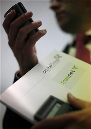 An employee of German mobile service provider Debitel checks his mobile phone as he holds a folder following a news conference with German phone and Internet service provider Freenet AG in Hamburg April 28, 2008. German telecoms group Freenet has bought Debitel from private equity owner Permira for 1.63 billion euros ($2.54 billion) despite opposition from major shareholder United Internet. The deal catapults Freenet and Debitel to the number three spot among Germany's mobile phone operators with around 19 million combined customers and heralds a long-awaited consolidation in the overcrowded market. REUTERS/Christian Charisius (GERMANY)