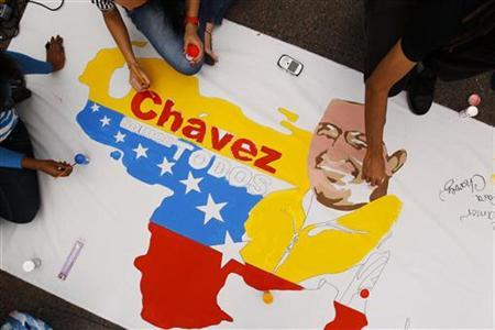 Followers of Venezuelan President Hugo Chavez paint a poster in support of him in Caracas December 14, 2012. Chavez suffered unexpected bleeding caused by a six-hour cancer operation in Cuba, the government said, although the ailing president's condition began to improve on Thursday. The poster reads: ''We are all Chavez''. REUTERS/Carlos Garcia Rawlins (VENEZUELA - Tags: POLITICS HEALTH)