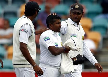 Sri Lanka's Rangana Herath (C) is congratulated by teammates after taking five wickets in the innings during the fourth day of play in the first test cricket test against Australia at Bellerive Oval in Hobart December 17, 2012. REUTERS/David Gray