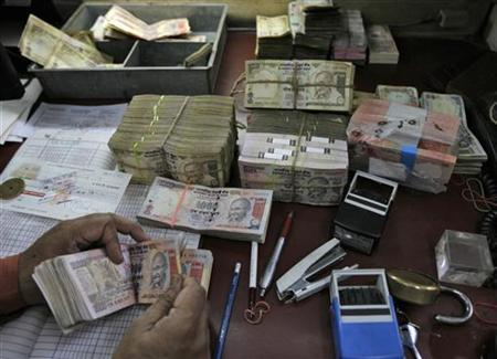 An employee counts rupee notes at a cash counter inside a bank in New Delhi June 8, 2010. REUTERS/Mukesh Gupta/Files