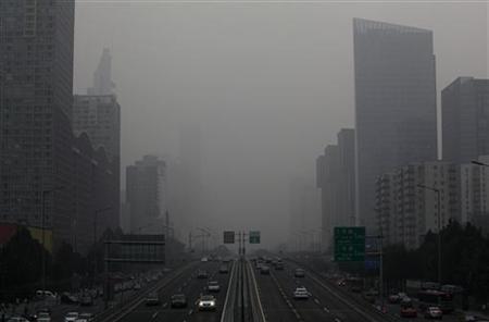 12月19日、大気汚染をもたらす有害な微小粒子状物質(PM2.5)が原因で今年、中国4都市で約8600人が死亡したことが明らかに。写真はスモッグでかすむ北京市内の道路。7月撮影(2012年 ロイター)