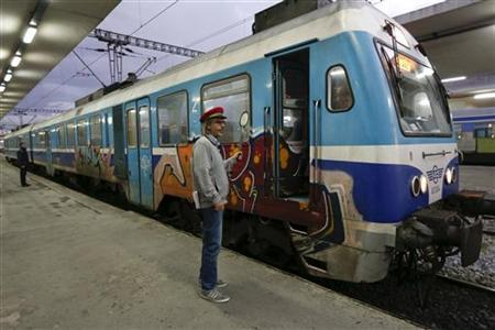 A train inspector signals to the train driver at Thessaloniki railway station, northern Greece November 29, 2012. Once an unpopular travel option, Greece's slow and creaky trains are winning new fans for the first time in decades as Greeks struggling with soaring fuel prices and high road taxes leave their beloved cars at home. Picture taken November 29, 2012. REUTERS/Yorgos Karahalis (GREECE - Tags: TRANSPORT SOCIETY BUSINESS)