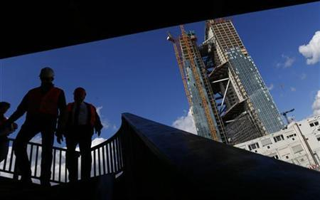 Construction workers walk down the stairs on a bridge next to the construction site of the new headquarters of the European Central Bank (ECB) in Frankfurt, September 19, 2012. The ECB will hold a topping out ceremony of the new building with ECB President Mario Draghi on Thursday September 20. REUTERS/Kai Pfaffenbach (GERMANY - Tags: BUSINESS POLITICS CONSTRUCTION)