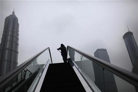 A cleaner works on an escalator at the Lujiazui financial district of Pudong in Shanghai May 14, 2012. REUTERS/Aly Song