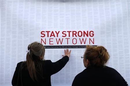 A woman touches a printout of messages from teenagers around the United States at a memorial for the victims of the Sandy Hook Elementary School shooting in Newtown, Connecticut December 18, 2012. REUTERS/Joshua Lott (UNITED STATES - Tags: CRIME LAW EDUCATION TPX IMAGES OF THE DAY)