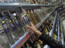 Покупатель берет с полки бутылку водки в российском супермаркете в Бенидорме 26 ноября 2012 года. Инфляция в России с 11 по 17 декабря 2012 года, седьмую неделю подряд, держится на отметке 0,1 процента, сообщил Росстат в среду. REUTERS/Heino Kalis