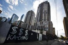 "A woman walks past graffiti which reads, ""KA-CHING"" near condominium buildings behind a lot of vacant land that is boarded up in Toronto September 21, 2012. REUTERS/Mark Blinch"