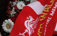 A football scarf lies with floral tributes at the Hillsborough memorial outside Liverpool Football Club's Anfield stadium in Liverpool, northern England December 19, 2012. Britain ordered a new investigation into the deaths of 96 soccer fans in the 1989 Hillsborough stadium disaster on Wednesday, three months after an independent report suggested the police had tried to cover up their mishandling of the tragedy. REUTERS/Phil Noble