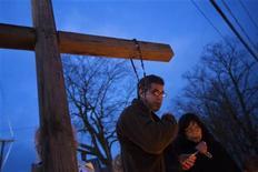 La localidad estadounidense de Newtown celebrará el miércoles servicios fúnebres por otras seis víctimas del tiroteo en la escuela primaria Sandy Hook, entre ellas el de la directora del colegio que fue asesinada junto a 20 estudiantes y cinco miembros de su personal. En la imagen, una pareja reza junto a una cruz en honor de las víctimas de la escuela, en Newtown, el 18 de diciembre de 2012. REUTERS/Lucas Jackson