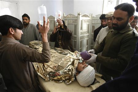 An anti-polio drive campaign worker, Hilal Khan (C), who was shot and badly injured by unidentified gunmen, lies at Lady Reading Hospital in Peshawar December 19, 2012. REUTERS/Khuram Parvez