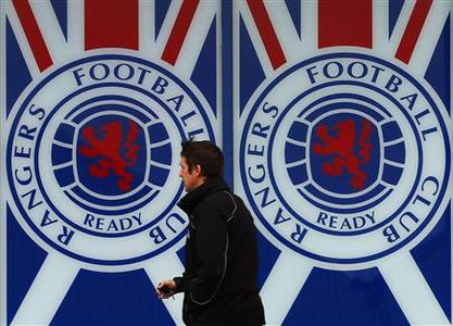 A man walks past a Rangers' soccer club poster at their Ibrox Stadium in Glasgow, Scotland December 19, 2012. REUTERS/David Moir