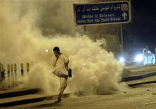 "A demonstrator kicks a tear gas canister away during clashes with anti-riot police at a protest against the election results in Kuwait in this December 4, 2012 file photo. In a room scented with incense, twelve men in long traditional robes sip sweet tea and debate the future for Kuwait's tribes at one of many ""diwaniya"" across the country, a tradition of evening social gatherings older than Kuwait itself. In the Saber al-Nasser area where the diwaniya took place some 20 km (12 miles) outside Kuwait City, police had to use tear gas and make arrests to disperse local youths protesting the voting changes in rare clashes in recent weeks. To match Feature KUWAIT-TRIBES/ REUTERS/Obaida al Ahmad/Files"