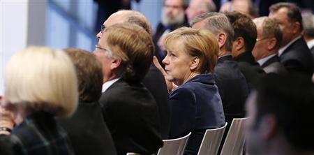 German Chancellor Angela Merkel (C) reacts during the commemoration of the new 380-kV high voltage power line between Schwerin and Hamburg, in Schwerin December 18, 2012. REUTERS/Morris Mac Matzen