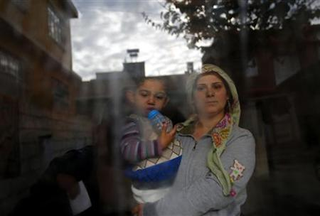 A Syrian refugee woman holds her son as she stands at the window of their friend's house at the Syrian-Turkish border town of Ceylanpinar, Sanliurfa province, December 6, 2012. REUTERS/Laszlo Balogh