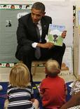 """Президент Барак Обама держит в руках детскую книжку на встрече с детьми в Eastfield College в Мескито, Техас 4 октября 2011 года. Журнал Time назвал Обаму """"человеком года"""" и отметил историческое значение его отразившего меняющийся этнический состав нации переизбрания вопреки экономическим проблемам. REUTERS/Larry Downing"""