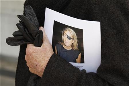 A man holds a sign honoring Sunday Times journalist Marie Colvin after a memorial service, outside St Martin in the Field in London May 16, 2012. REUTERS/Stefan Wermuth/Files