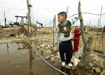 Мальчик и девочка стоят у забросанного мусором пруда в лагере беженцев на нефтяном месторождении рядом с Баку 8 ноября 2005 года. Баку в среду сообщил о вводе в эксплуатацию первого завода утилизации, чтобы справиться с потоком бытовых отходов, растущим на фоне увеличения благосостояния экспортирующей нефть страны. REUTERS/David Mdzinarishvili