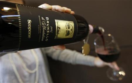 A woman fills a glass with Brunello di Montalcino red wine at the Vinitaly wine expo in Verona, April 8, 2011. REUTERS/Stefano Rellandini