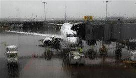 A Westjet aircraft is seen through a rain-covered window at Trudeau airport in Montreal May 16, 2011. REUTERS/Shaun Best