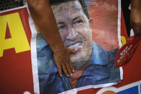 A supporter of Venezuelan President Hugo Chavez touches a poster of him while participating in a campaign rally of United Socialist Party of Venezuela (PSUV)'s candidate for Miranda state governor, Elias Jaua, in Los Teques outside Caracas in this December 13, 2012 file photograph. REUTERS/Jorge Silva/Files