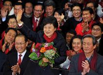La hija del ex mandatario militar de Corea del Sur ganó las elecciones presidenciales del miércoles, convertiéndose en la primera jefa de Estado del país, prometiendo trabajar por reparar a una sociedad dividida. En la imagen, la candidata a la presidencia de Corea del Sur Park Geun-Hye saluda con un ramo de flores en la mano tras llegar a la sede de su partido en Seúl, el 19 de diciembre de 2012. REUTERS/Kim Jae-Hwan/Pool