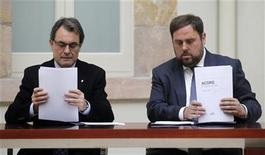 The centre-right Convergence and Union (CiU) leader Artur Mas (L) and Republican Left (ERC) leader Oriol Junqueras sign an agreed alliance at Parlament de Catalunya in Barcelona, December 19, 2012. REUTERS/Albert Gea