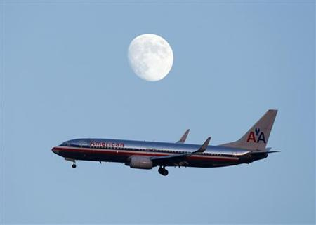 An American Airlines passenger jet glides in under the moon as it lands at LaGuardia airport in New YorkNew York, August 28, 2012. REUTERS/Eduardo Munoz