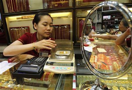 An employee weighs gold rings at a gold shop in Hanoi August 23, 2011. REUTERS/Kham/Files