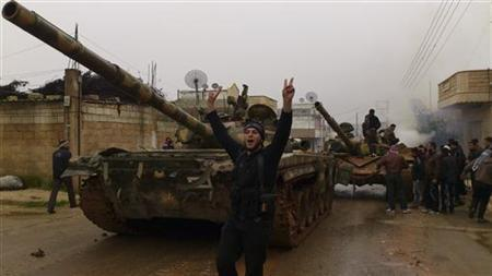 Free Syrian Army fighters from Al-Farooq battalion celebrate near tanks after the fighters said they fought and defeated government troops in Halfaya, near Hama December 18, 2012. REUTERS/Samer Al-Hamwi/Shaam News Network/Handout