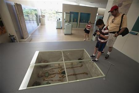 A child takes a picture of a Mayan skeleton at the Museum of Mayan Culture in Cancun, December 19, 2012. REUTERS/Victor Ruiz Garcia