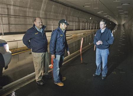 Governor Andrew Cuomo (R), tours the damaged Hugh L. Carey Tunnel with MTA Chairman Joseph J. Lhota (L) and Jim Ferrara, President of MTA Bridges and Tunnels October 30, 2012 in this handout photo supplied by the Metropolitan Transportation Authority (MTA) October 31, 2012. REUTERS/MTA/Patrick Cashin/Handout
