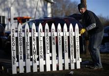Mike Garbowski of Newtown, Connecticut begins to erect a fence he built that will bear the names of all of those killed in the December 14 shootings at the Sandy Hook Elementary School in Sandy Hook village in Newtown, December 19, 2012. Six funerals for victims of the shootings were being held Wednesday in the Newtown area. REUTERS/Mike Segar