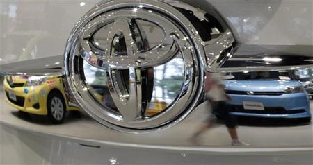 A visitor walking past cars is reflected on a Toyota car at the company's showroom in Tokyo October 18, 2012. REUTERS/Toru Hanai