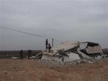 Children stand on a house damaged by what activists said were missiles fired by a Syrian Air Force fighter jet of forces loyal to Syria's President Bashar al-Assad at Tel Abyed near Hasaka December 17, 2012. REUTERS/Samer Al-Abdullah/Shaam News Network/Handout