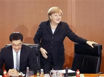 German Chancellor Angela Merkel takes her seat next to Economy Minister Philipp Roesler (L) before the weekly cabinet meeting in Berlin December 6, 2012. REUTERS/Wolfgang Rattay