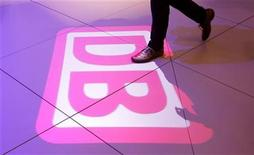 "A visitor passes a light installation of the logo of German rail operator Deutsche Bahn during the opening day of the ""Innotrans"" fair (International Trade Fair for Transport Technology - Innovative Components, Vehicles, Systems) in Berlin, September 18, 2012. REUTERS/Tobias Schwarz (GERMANY - Tags: BUSINESS TRANSPORT)"