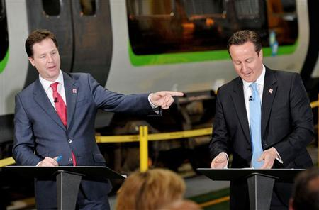 File photo of British Prime Minister David Cameron (R) and Deputy Prime Minister Nick Clegg speaking at London Midland railway's Soho depot in Smethwick July 16, 2012. REUTERS/Tim Ireland/POOL