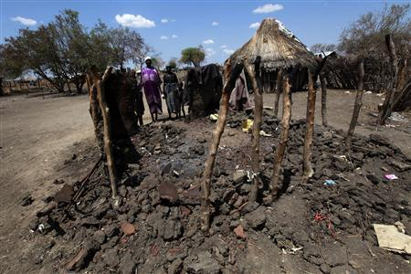 File photo of a family from the Murle tribe standing near a burned out shelter in Pibor after ethnic clashes, April 4, 2012. REUTERS/Mohamed Nureldin Abdallah