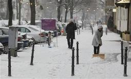 A woman clears snow outside a shop in Berlin December 9, 2012. Heavy snowfalls hit the German capital on Sunday. REUTERS/Wolfgang Rattay (GERMANY - Tags: ENVIRONMENT)
