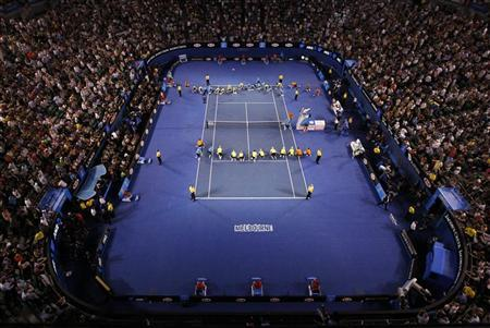 The court is being dried during a rain delay at the men's singles final match between Novak Djokovic of Serbia and Rafael Nadal of Spain at the Australian Open tennis tournament in Melbourne January 29, 2012. REUTERS/Daniel Munoz
