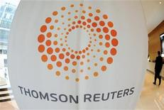 A man walks near a Thomson Reuters logo at the Thomson Reuters building in Canary Wharf in east London May 7, 2009. REUTERS/Toby Melville