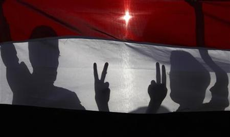 Boys posing with the victory sign are silhouetted against Yemen's national flag at a rally in Sanaa September 18, 2012, commemorating people killed during last year's unrest against former Yemeni president Ali Abdullah Saleh. REUTERS/Mohamed al-Sayaghi