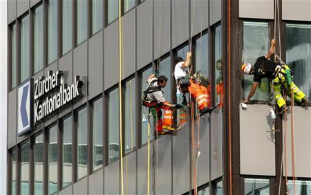 Workers clean the windows at an office building of Swiss regional bank Zuercher Kantonalbank (ZKB) in Zurich September 20, 2011. REUTERS/Arnd Wiegmann