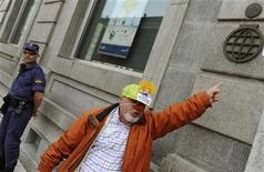 A man points at a logo next to a policeman as he takes part in a protest outside the Liberbank headquarters in Oviedo, northern Spain, May 28, 2012. REUTERS/Eloy Alonso