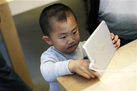 A child looks at an iPad mini at the Apple Store during Black Friday in San Francisco, California, November 23, 2012. REUTERS/Stephen Lam/Files